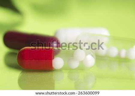 pills with homeopathy globules in  green background  - stock photo