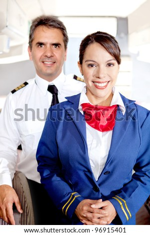 Pilot and air hostess in an airplane cabin smiling - stock photo
