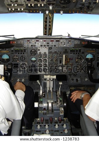 Pilot and copilot operating boeing 737 plane - inside cockpit - stock photo