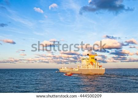 Pilot boat maneuvers next to tanker ship on sea - stock photo