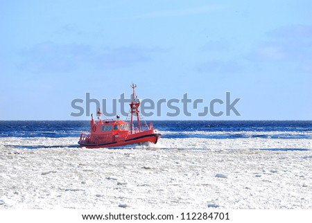 Pilot boat sailing through ice near port of Riga - stock photo