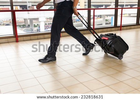 pilot carries his luggage at the airport terminal - stock photo