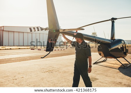 Pilot checking tail wings helicopter during preflight checklist on a sunny day. Engineer doing pre flight inspection. - stock photo