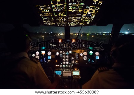 Pilot in airplane cockpit night - stock photo