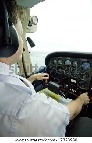Pilot in cockpit flying an airplane - stock photo