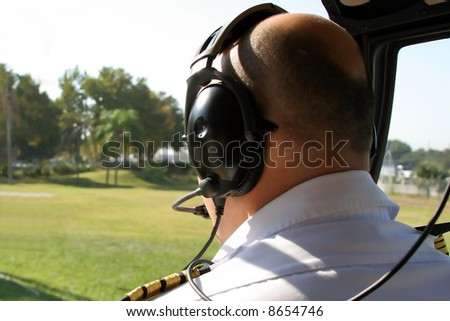 pilot in cockpit of helicopter - stock photo