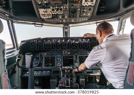 Pilot in the cockpit of a passenger plane - stock photo