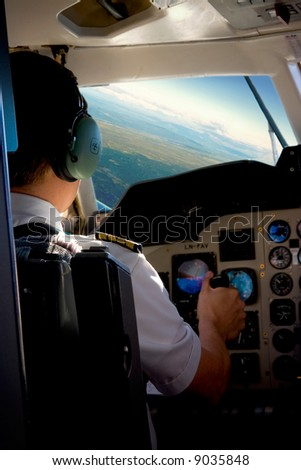 Pilot in the cockpit of a small commercial aircraft above a rural landscape. - stock photo