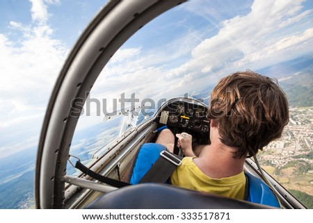 pilot in the cockpit of an aircraft which flies over the landscape - stock photo