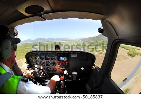 Pilot landing a small plane on Cairns airport, Australia after scenic flight - stock photo