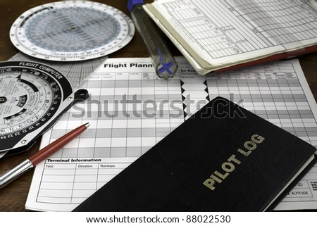 pilot log on a wooden table with headset, fuel tester and plotter - stock photo
