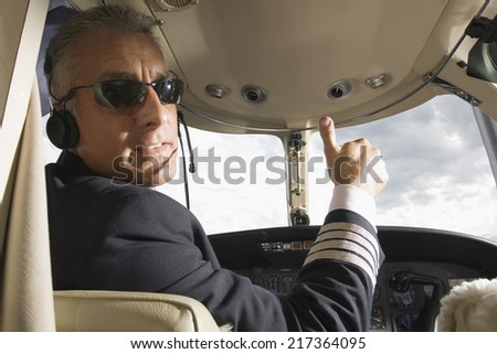 Pilot making thumbs up sign in the cockpit of a private airplane - stock photo