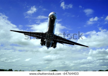 Pilot navigates jet flying just above the trees coming in for a landing. Landing gear is present and running lights are on for a clear shot of the airfield. - stock photo