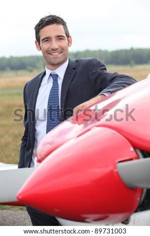 Pilot next to plane - stock photo
