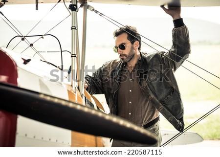 Pilot preparing his airplane - stock photo