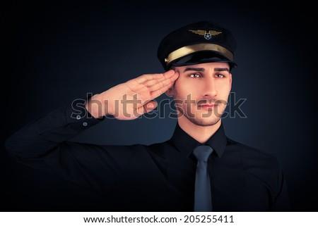 Pilot Salute Low Key Portrait - Young pilot wearing black shirt and tie salute portrait on black background   - stock photo