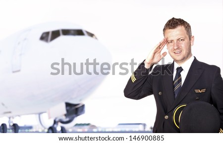 Pilot saluting in front of airplane - stock photo