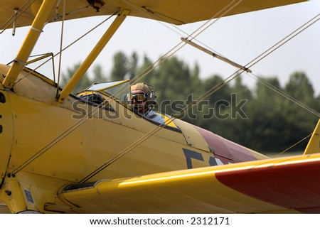Pilot taxing a restored WWI biplane - stock photo