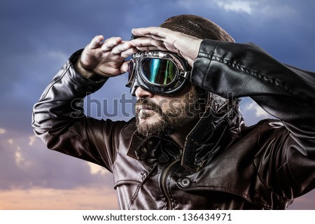 pilot with glasses and vintage hat with proud expression looking at the horizon - stock photo