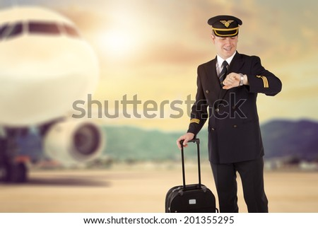 pilot with luggage checks his watch - stock photo