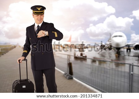 pilot with luggage on airport - stock photo