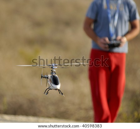 Piloting Radio controlled helicopter with remote control - stock photo