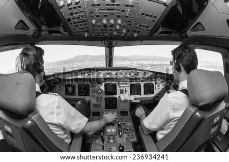 Pilots in an airplane cockpit - stock photo