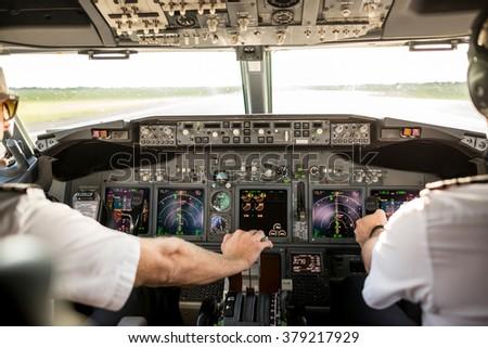 Pilots in cockpit - stock photo