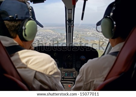 Pilots in helicopter cabin - stock photo