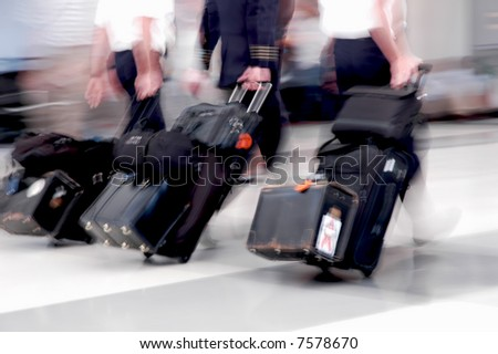 Pilots in motion rushing through an airport - stock photo