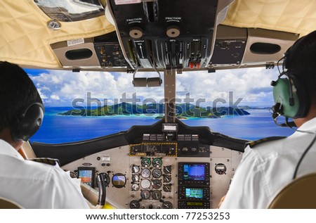 Pilots in the plane cockpit and tropical island - stock photo