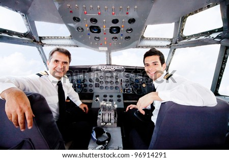 Pilots sitting in an airplane cabin flying and smiling - stock photo