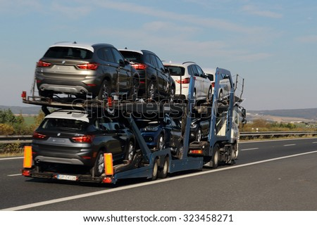 PILSEN, CZECH REPUBLIC - OCTOBER 2, 2015: Truck carrying new BMW cars on the D5 highway. The D5 is important transport connection between West Bohemia and Bavaria in Germany. - stock photo