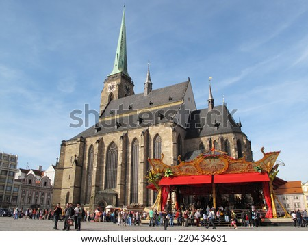 PILSEN, CZECH REPUBLIC - SEPTEMBER 28, 2014: Square with cathedral of St. Bartholomew and carrousel Le Manege Carre Senart. Pilsen city celebrate title of the European Capital of Culture 2015. - stock photo