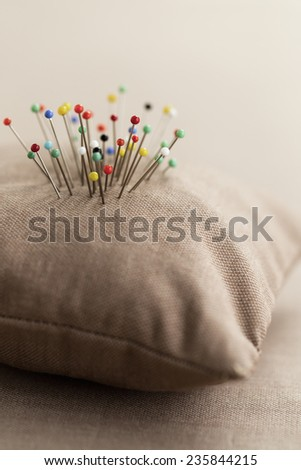 Pin cushion with multi-coloured pins in it - stock photo