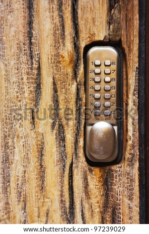 PIN keypad with numbers and letters carved in the wooden door - stock photo