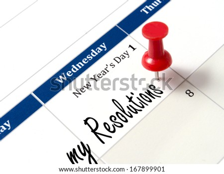 Pin on calendar pointing new year resolutions close up - stock photo