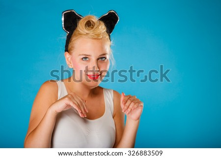 Pin up and retro style. Young smiling woman with black ears pretending mouse on head on blue background. Studio shot. - stock photo