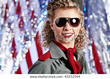 Pin-up army woman  standing near the American flag - stock photo