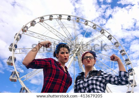 Pin up friends making funny gym position in front of ferris wheel - Girls having fun together outdoor - Retro vintage fashion concept - Saturated filter