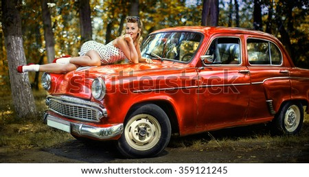 Pin-up girl in white dress on the hood of red retro car on a background of green forest - stock photo