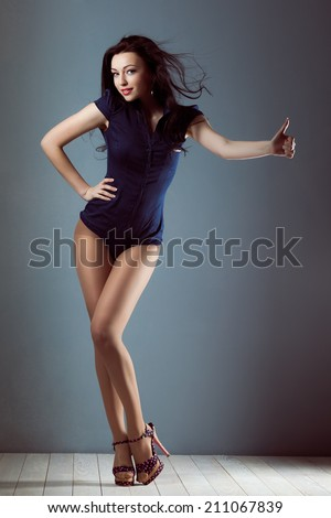 Pin up girl sexy with flying hair in overalls body swimsuit in shoes hitchhiking - stock photo