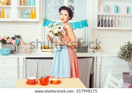 Pin-up girl style. Girl standing in the kitchen and holding a vase in which the flowers. - stock photo