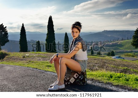 Pin up girl. Stylish hitchhiker young woman sits on the suitcase on a rural road. Tuscan, Italy - stock photo