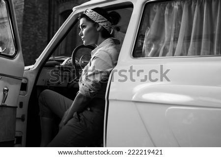 pin-up lady wearing shirt in retro car - stock photo