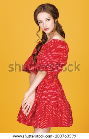 Pin-up of young beautiful girl with curly hair in a red dress on a yellow background.