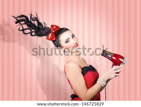 Pin-up portrait of a brunette fashion model with long straight hair blow drying with retro hairdryer. Hair care concept - stock photo