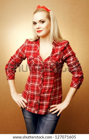 Pin-up portrait of a pregnant beautiful housewife in casual clothes posing over wooden background. Studio shot - stock photo