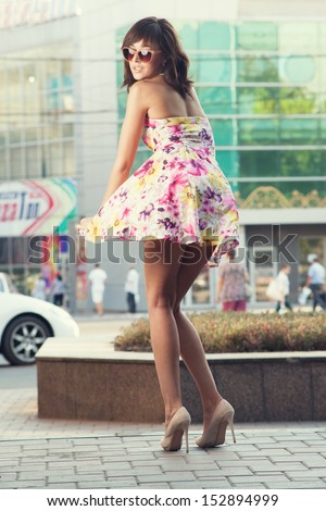 pin-up style girl on street. the wind blows up her skirt - stock photo