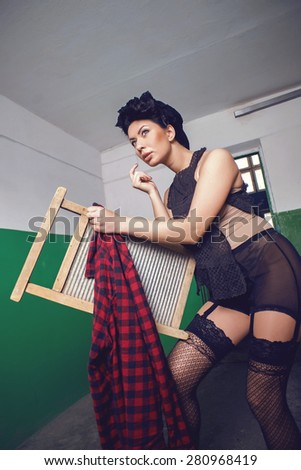 Pin up, vintage style photo of woman doing laundry. - stock photo